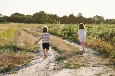 Happy children running on meadow in summer in nature.