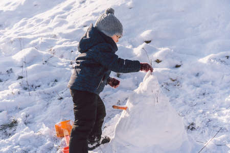 Little boy playing with snow. Winter holiday.