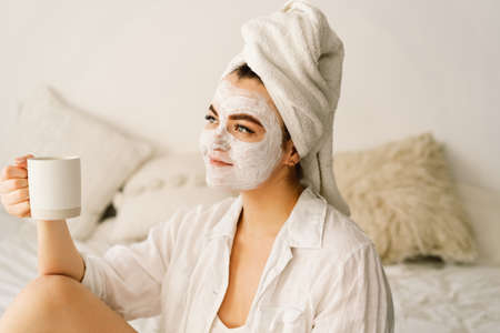 Beautiful woman applying facial mask and drinking tea in bed. Lifestyle