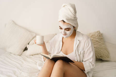 Beautiful woman applying facial mask, reading book and drinking tea in bed. Lifestyle