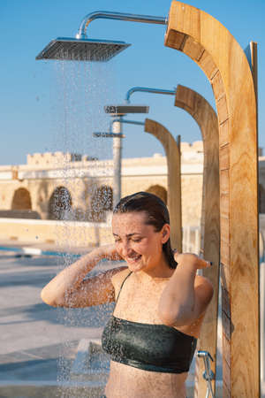 Beautiful young woman takes a relaxing shower in a swimsuit on a sunny day outdoors by the sea. Lifestyle