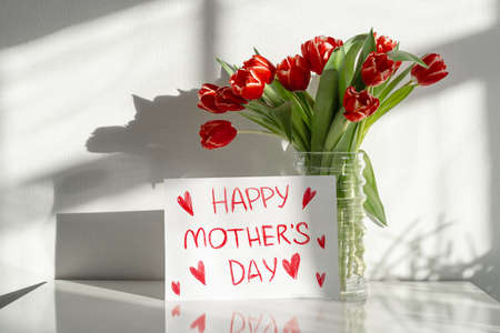 Happy Mother's Day. A bouquet of red tulips on the dresser in the living room.