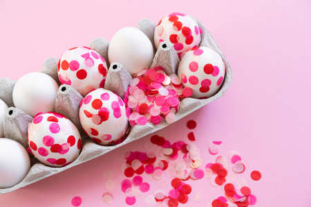 Happy Easter. Easter eggs decoration pink paper confetti.