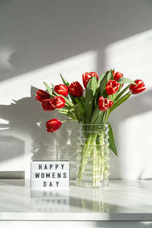Happy Women's Day. A bouquet of red tulips on the dresser in the living room. Stock fotó