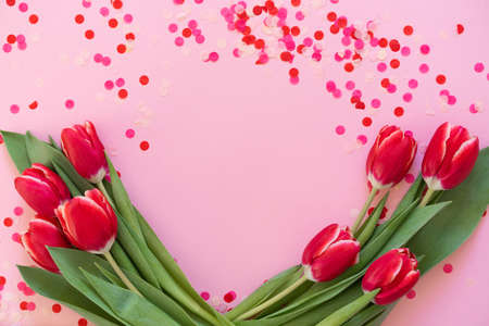 Greeting card. Red tulips with pink confetti on pink background Stock fotó