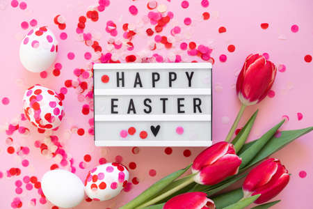 Happy Easter. Easter eggs decorated with paper confetti and tulips