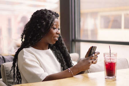 African woman using phone in cafe. People and technology