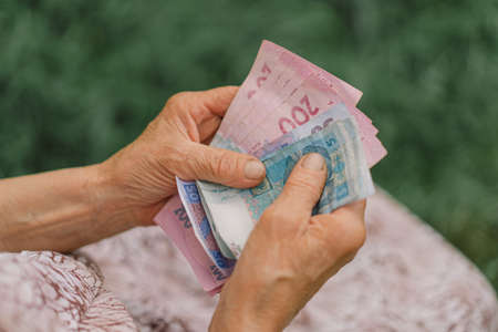 Concerned elderly woman counting Ukrainian money hryvnia. The concept of old age, poverty, austerity. 版權商用圖片