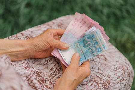 Concerned elderly woman counting Ukrainian money hryvnia. The concept of old age, poverty, austerity.
