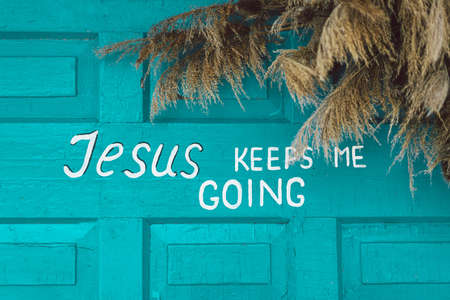 Text Jesus keep me going on a wooden turquoise background. Religious poster