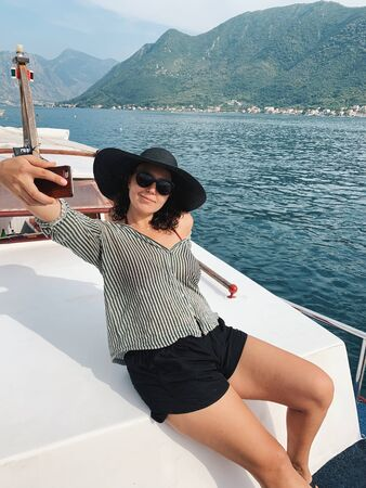 Caucasian woman taking selfie sitting on luxury yacht with amazing beauty landscape at sunny day.