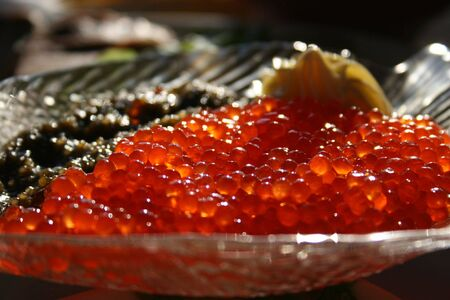 dearly: It is a lot of red and black caviar in a plate on a table.
