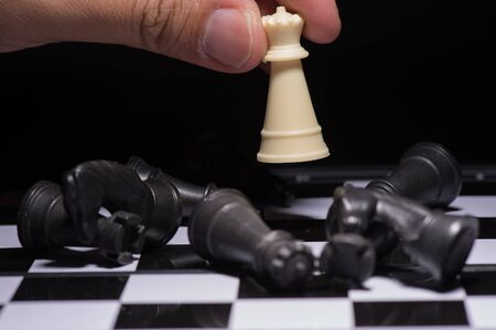 outwit: One  chess pieces staying against black chess pieces Stock Photo
