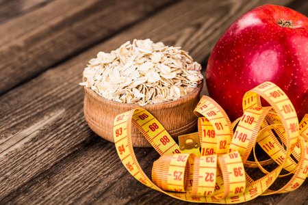 ensuring: Healthy bowl of muesli, apple, fruit, nuts and milk for a nutritious breakfast with a low glycemic index ensuring plenty of energy for the day Stock Photo