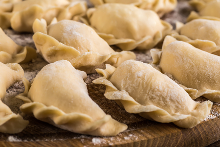 semifinished: Sculpt pierogy,  cutting board, making  on a  wooden table. Stock Photo