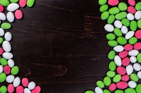dragee: Colorful candy and lollipops. Isolated on a dark wooden background