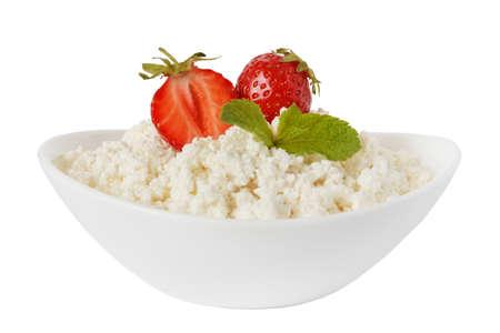 queso fresco blanco: el requesón en un cuenco con fresas aisladas sobre un fondo blanco Foto de archivo