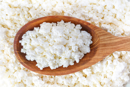 crumbly cottage cheese in the wooden spoon lying on the cottage cheese Stock Photo