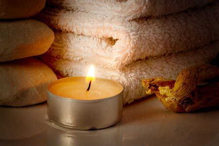 restful: restful image of burning candle on a background of white towels Stock Photo