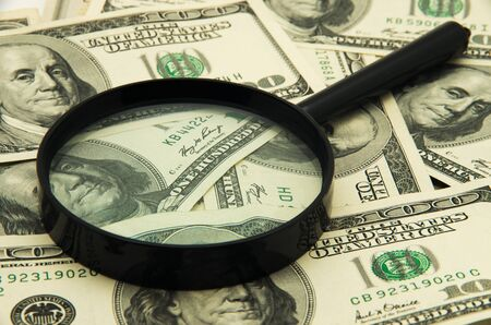 looking glass: Magnifying glass and money - business background