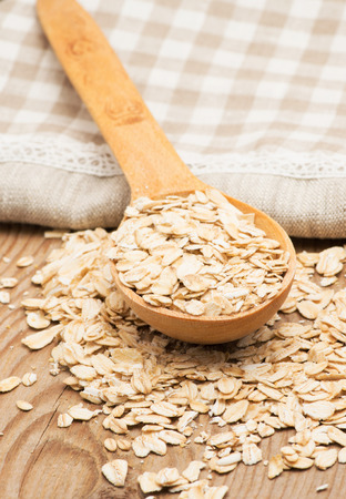 homespun: Whole grain, rolled oats with wooden spoon and homespun napkin. Stock Photo