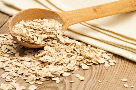 Whole grain, rolled oats with wooden spoon and homespun napkin. photo