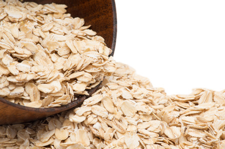 Oats spilling from wooden bowl.