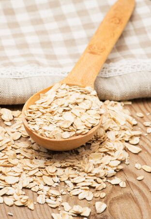 rolled oats: Whole grain, rolled oats with wooden spoon and homespun napkin. Stock Photo