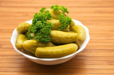 gherkins: Plate with small canned gherkins on wooden background.