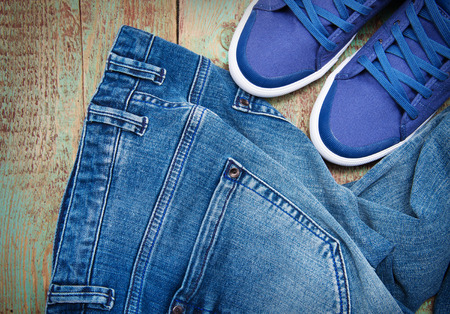 Pair of jeans thrown on floor with a pair of sneakers photo