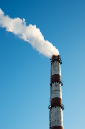 harming: Smoke from a chimney on blue sky background Stock Photo