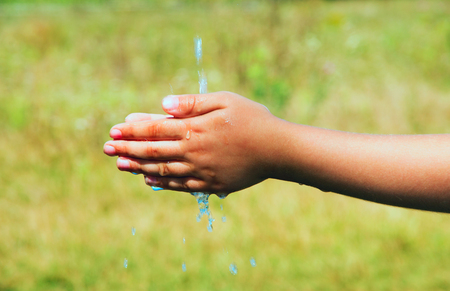 spring water: A young child is washing his hand.