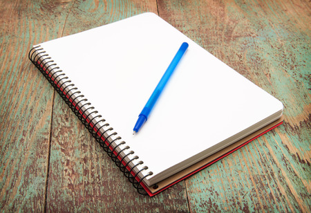 spiral notebook and pen on wooden desk