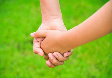 tenderness: Mother holding a hand of his son in summer day outdoors Stock Photo