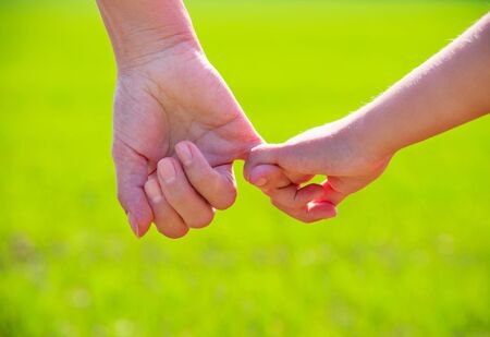mum and child: a parent holds the hand of a small child Stock Photo