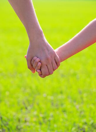 hold hands: Mother holding a hand of his son in summer day outdoors Stock Photo