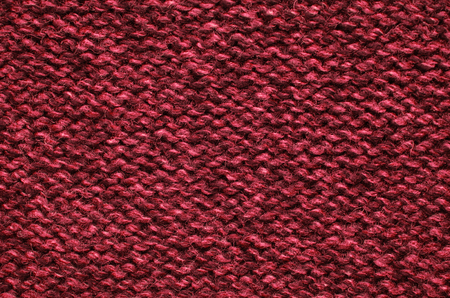 tejido de lana: The texture of a knitted woolen fabric red.