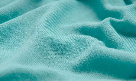 tejido de lana: The texture of a knitted woolen fabric turquoise.