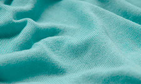 The texture of a knitted woolen fabric turquoise.