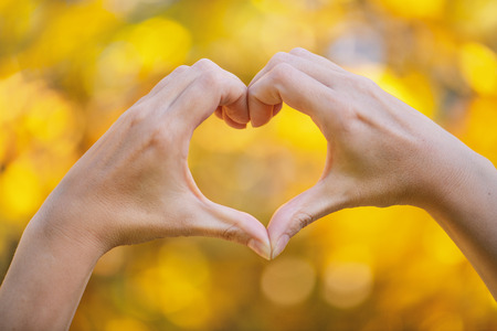 Hands in heart shape framing on nature background