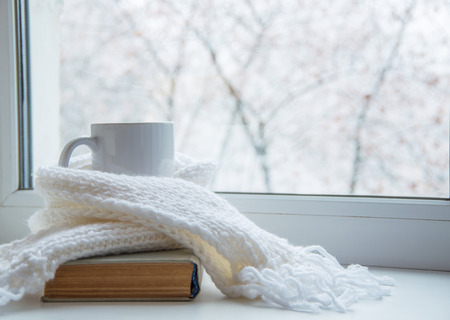 Mug of hot tea and warm woolen knitting on windowsill against snow landscape from outside. Reklamní fotografie