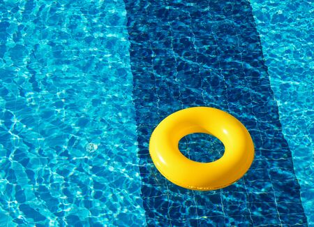Yellow pool float, ring floating in a refreshing blue swimming pool Stock fotó