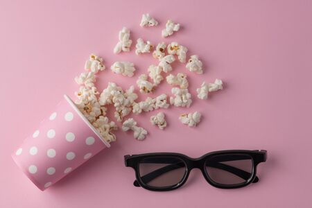 Popcorn, cup and 3d glasses on a pastel pink background.