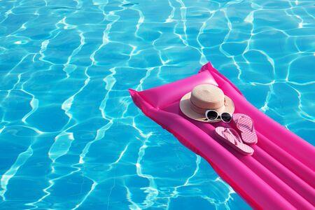 Fondo de vacaciones de verano en la playa. Colchón inflable de aire, chanclas y gorro en piscina.