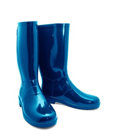 Botas de goma azul sobre un fondo blanco. Foto de archivo