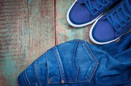 Pair of jeans thrown on floor with a pair of sneakers