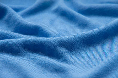 The texture of a knitted woolen fabric blue.