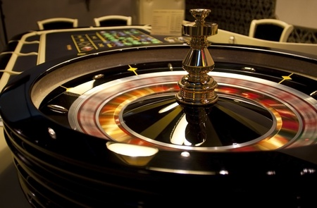 Rotating roulette in casino on background of table and chairs.