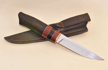 Old hunting knife in  leather case on light background