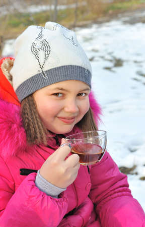 Portrait of girl in winter clothes, drinking tea outdoors